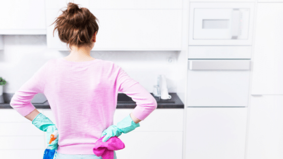 Back of a woman looking at clean kitchen