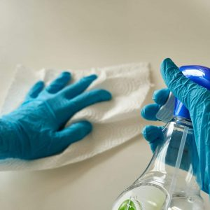 hands with gloves disinfecting a countertop